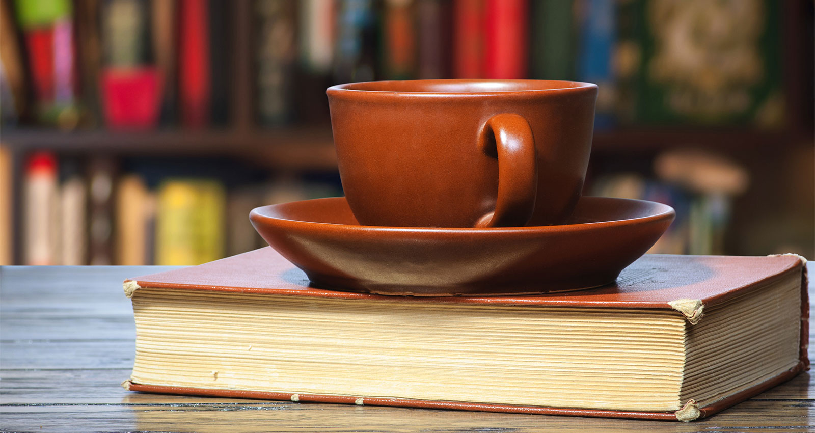 Cup and saucer place on top of a book.