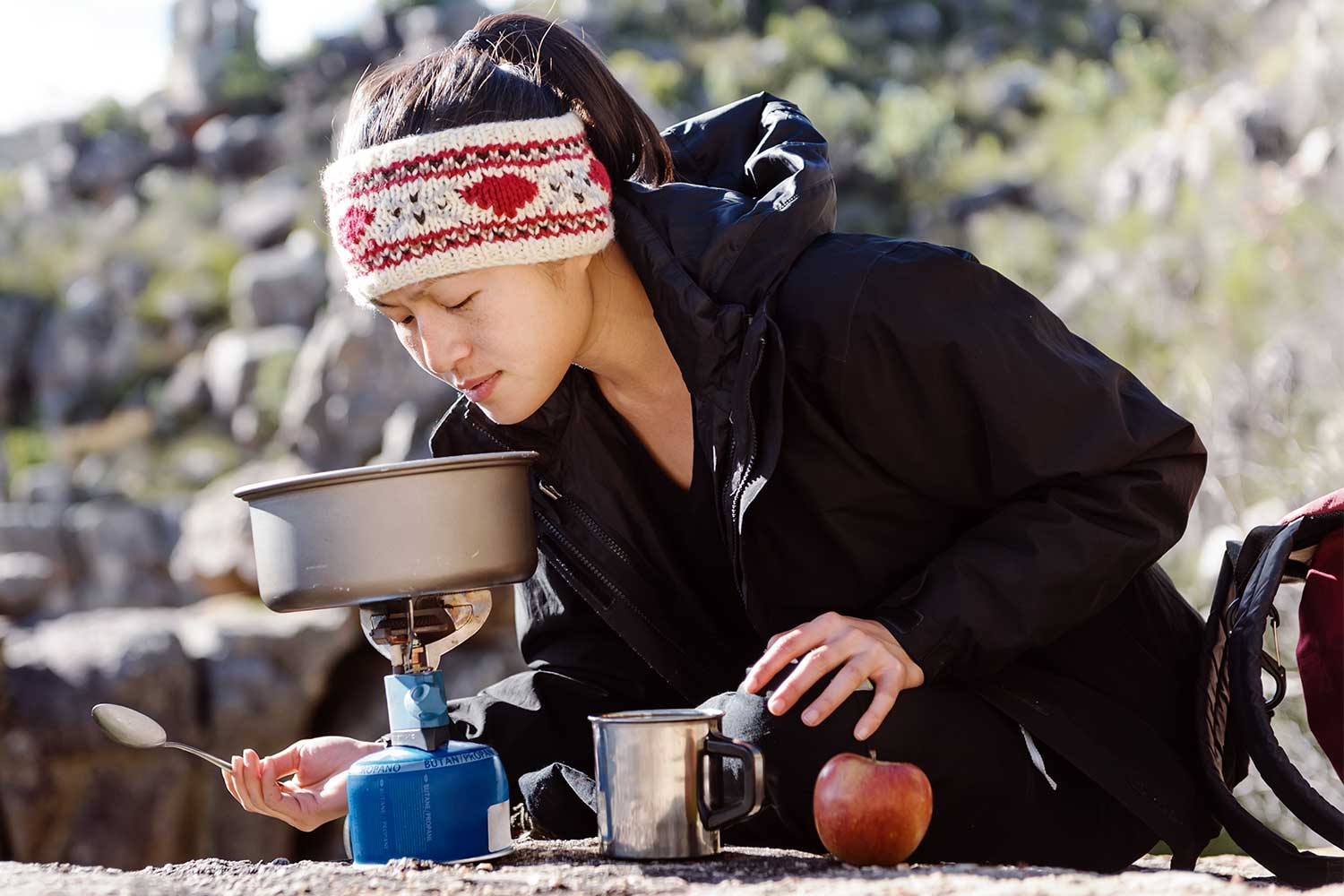 Woman cooking food on hiking stove.