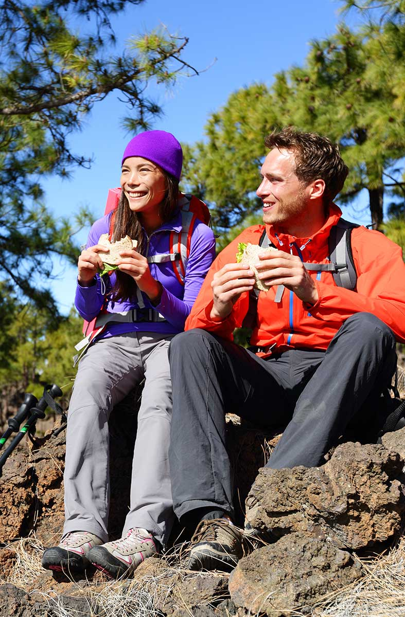 Man and woman eating a snack on a hike.