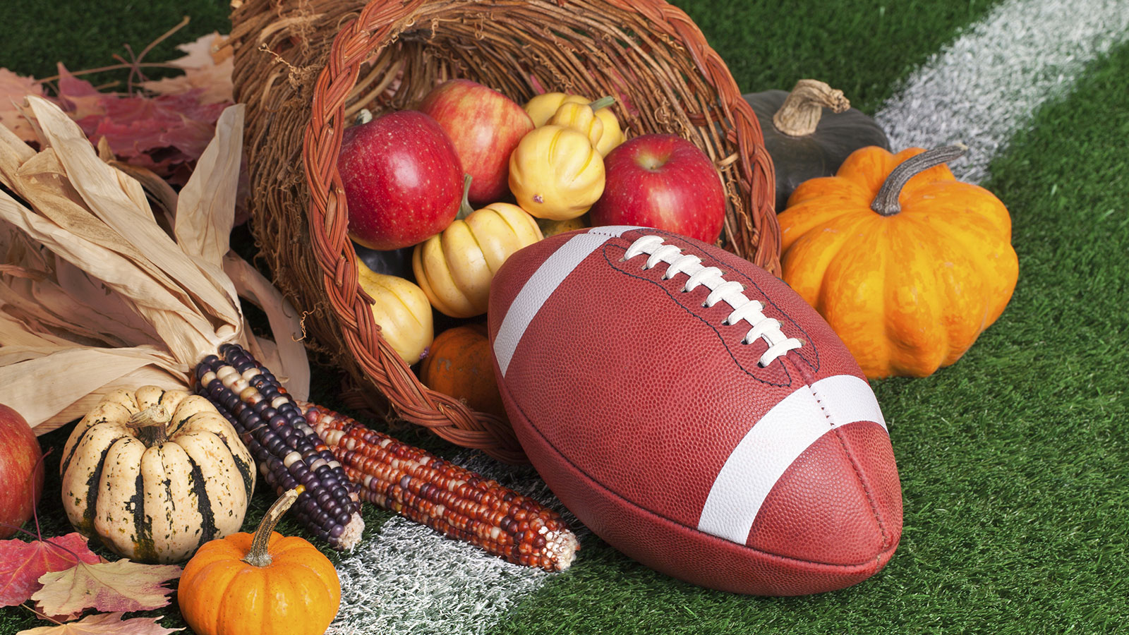 Thanksgiving cornucopia with football on football field.